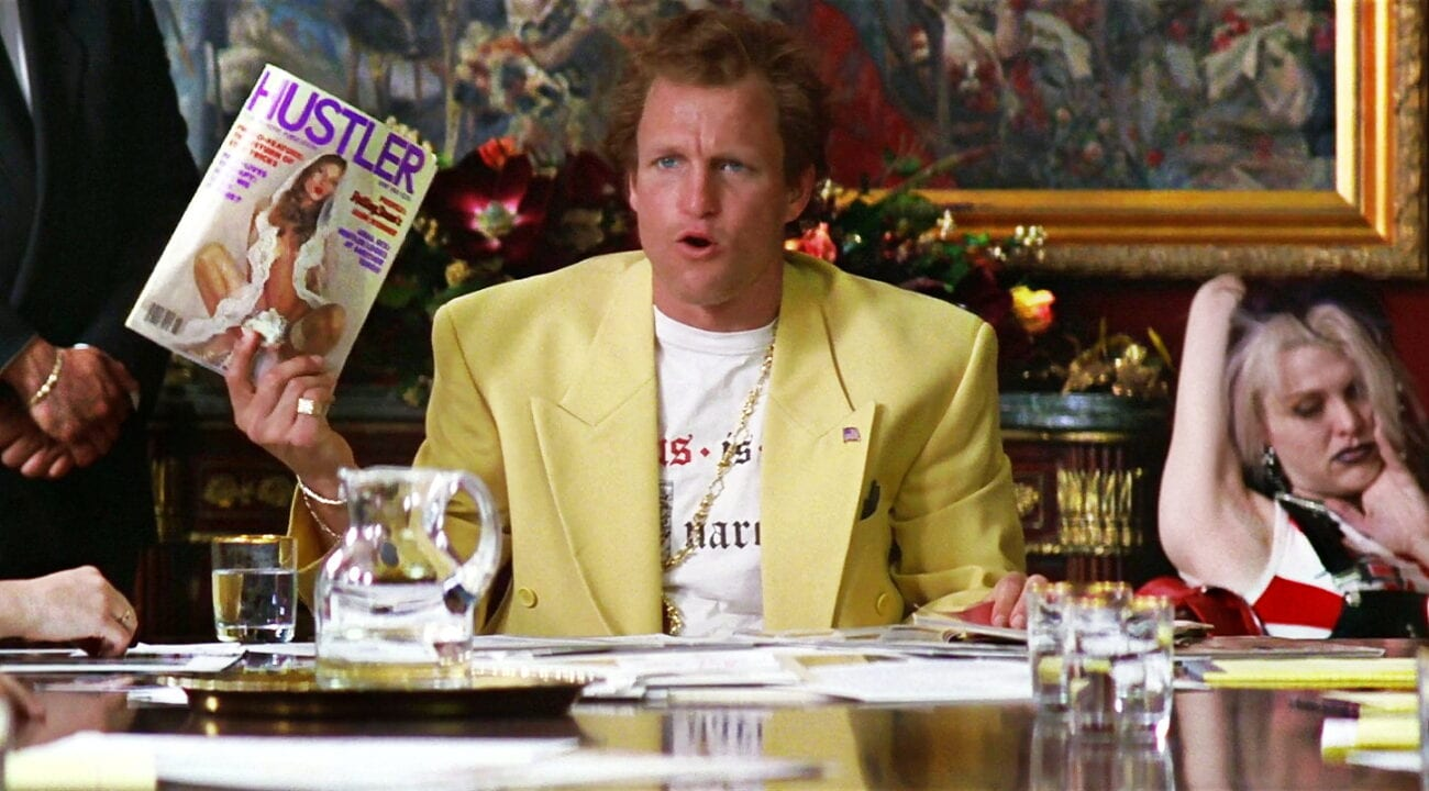 Larry Flynt holds up a copy of Hustler magazine while sitting at his desk