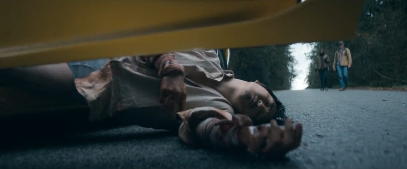The Stand S1E3 - A man has fallen out of the driver's side of a yellow sports car onto the road, two hunters in the background approaching