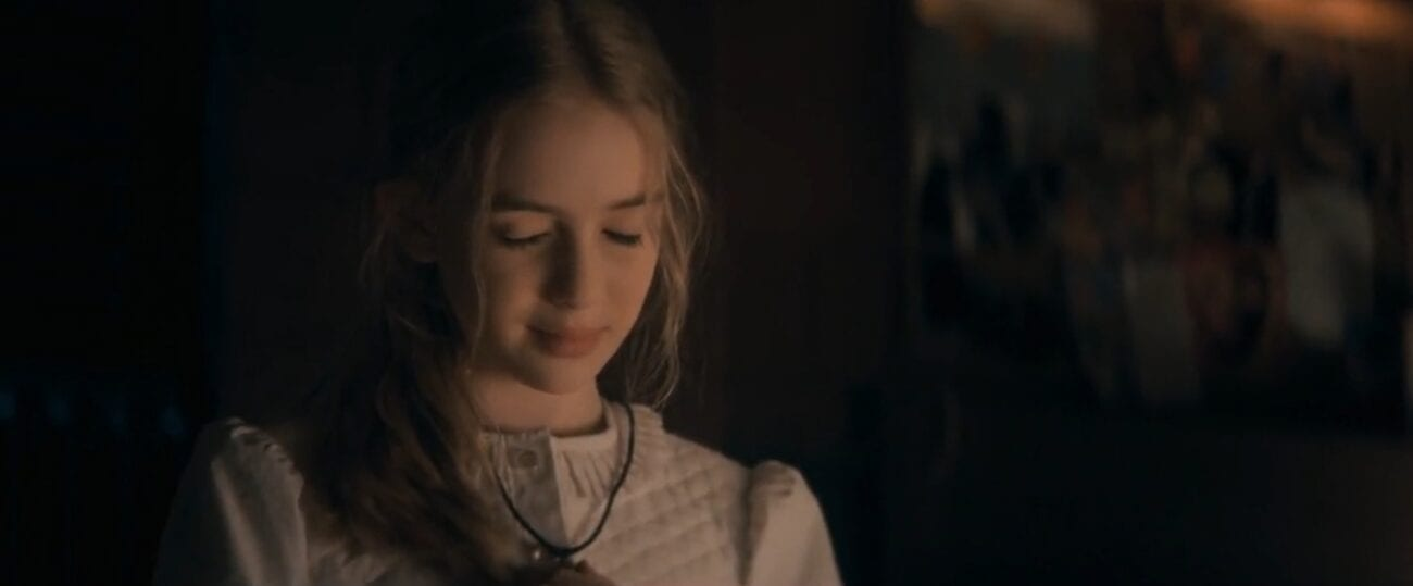 Young Nadine fingers her necklace, eyes closed and a slight smile on her face in The Stand Episode 3