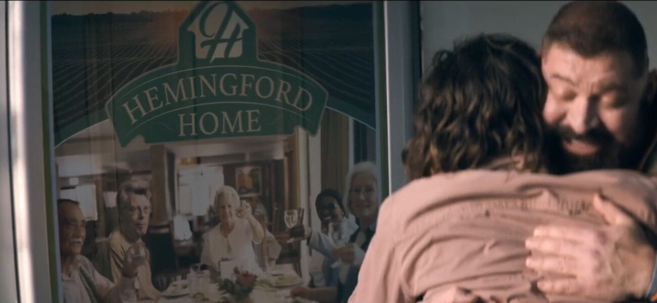 Tom embraces Nick, a poster advertising Hemingford Home behind them in The Stand Episode 4