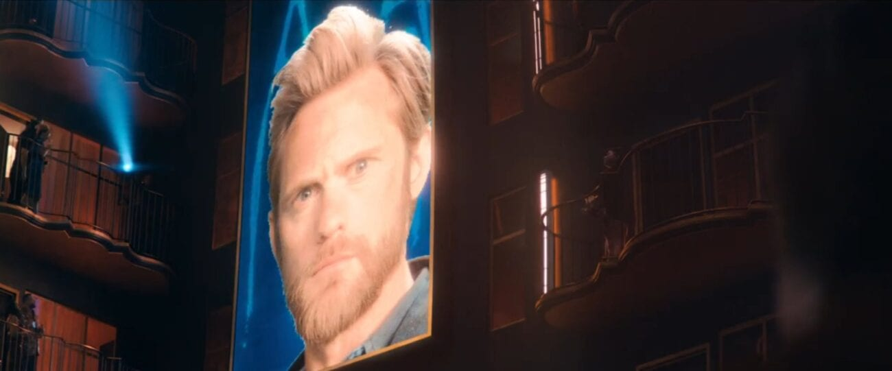 Flagg's face on a large jumbotron screen in a hotel interior in The Stand Episode 5
