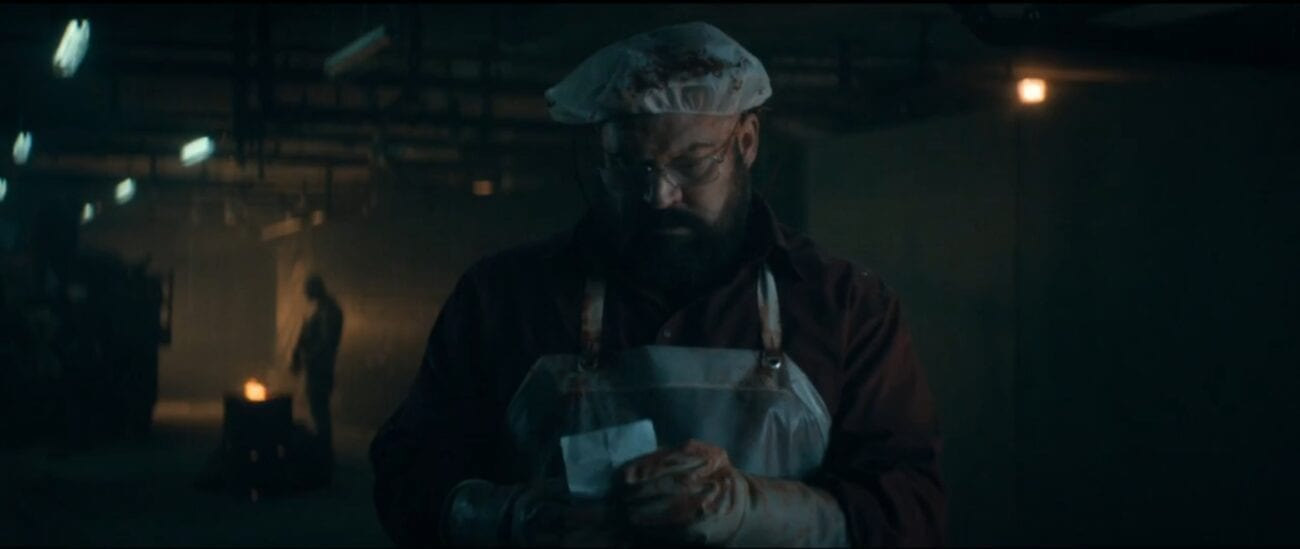 The Stand S1E5 - Tom Collen stand in bloodied butcher's apron holding a piece of paper in his hands