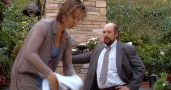 C.J. (Allison Janney) dries off with a towel while Toby (Richard Schiff) stands in front of brick wall and looks on