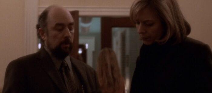 Toby (Richard Schiff) and CJ (Allison Janney) walking through a West Wing corridor