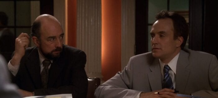 Toby (Richard Schiff) looks at Josh (Bradley Whitford) with his hand by his head, in the Mural Room