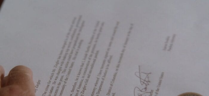 President Bartlet's thumb in the lower left, screen is filled with the text of Toby's pardon