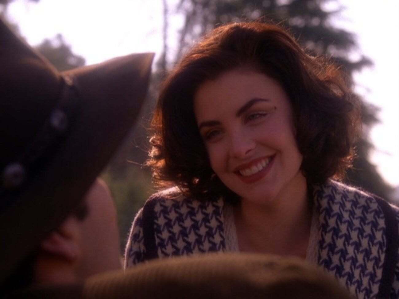 Audrey smiles at Jack, facing her in the foreground