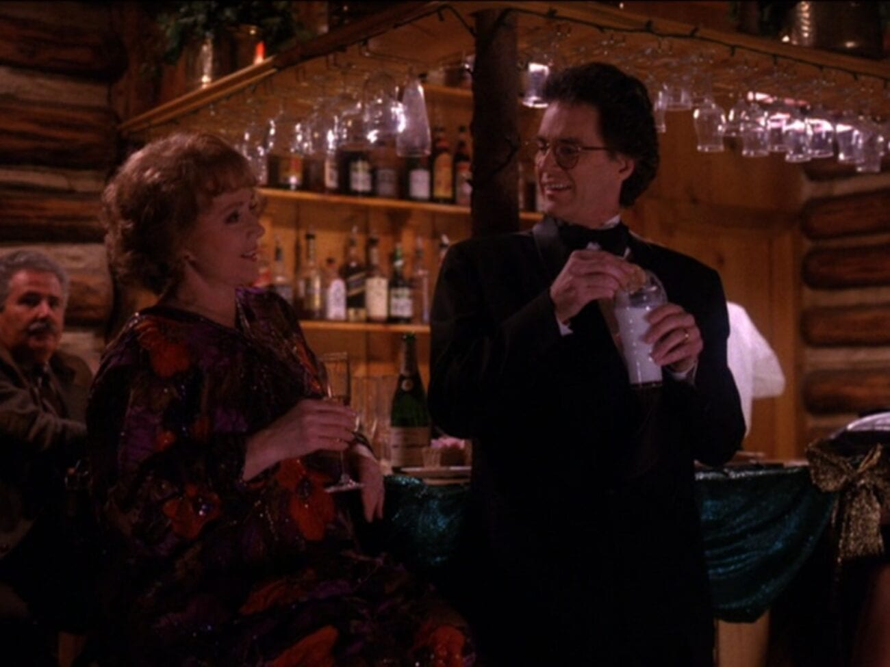 Catherine seated at a bar talking to Ben, standing and dipping a cookie in a glass of milk