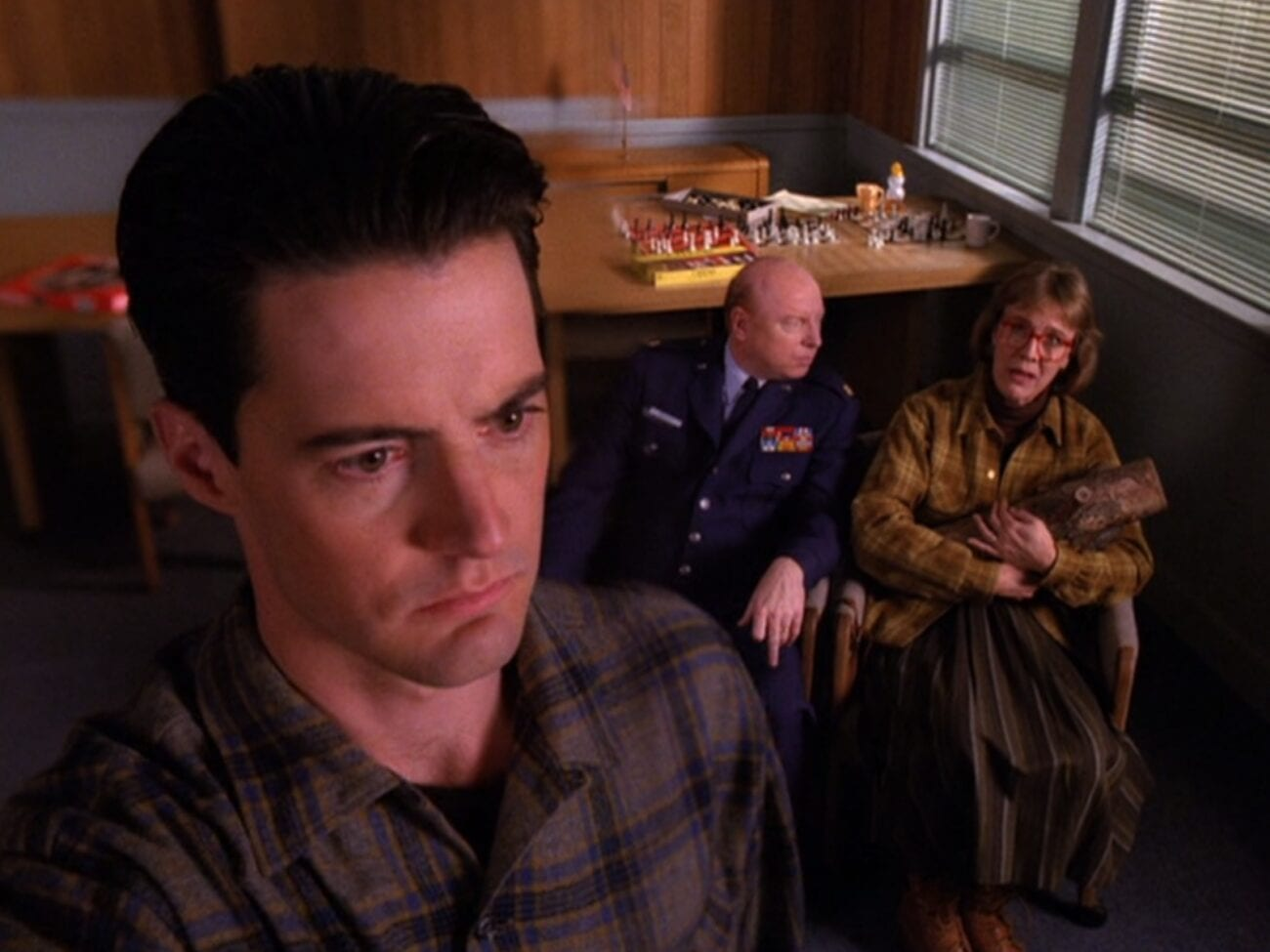 Cooper looks ahead in the foreground, Major Briggs and Log Lady sitting in the background, in the sheriff station conference room