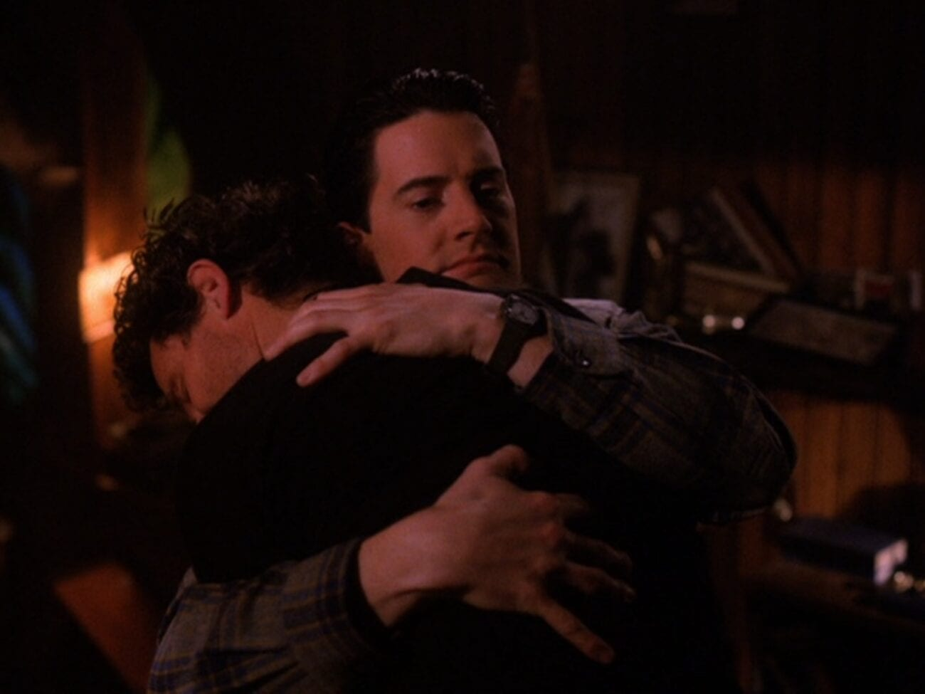 Cooper gives Harry a big hug, a destroyed Bookhouse in the background