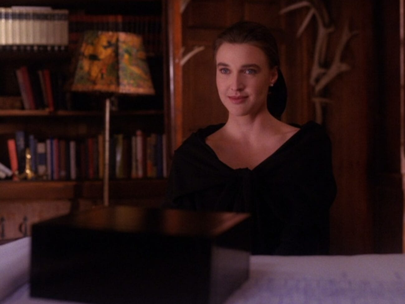 =ones, dressed in mourning black, sits at a desk, a large black box in front of her