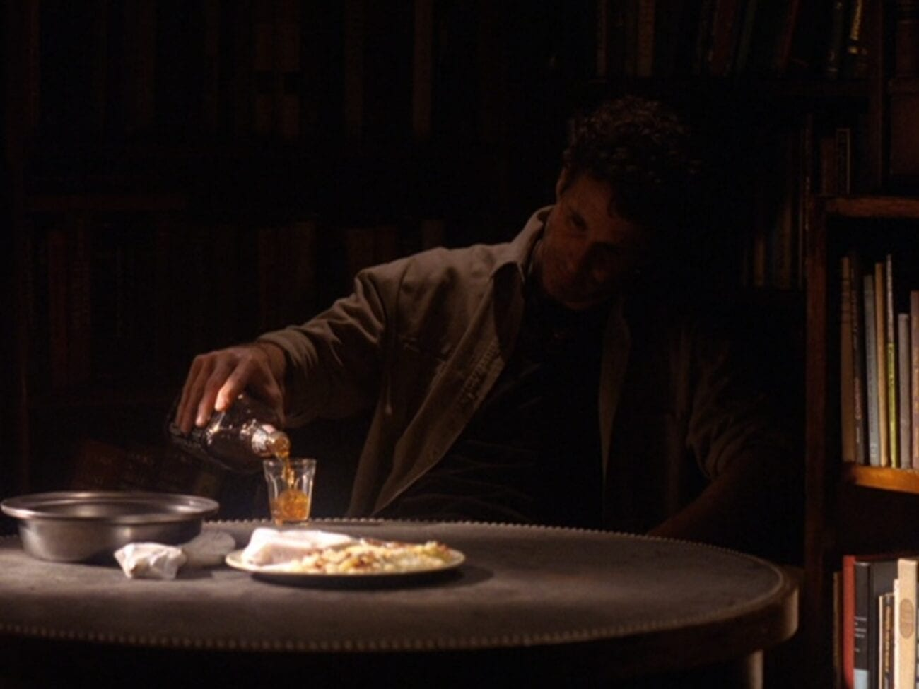Harry sits in dim light at a bare table with a plate of breakfast untouched, pouring himself a drink