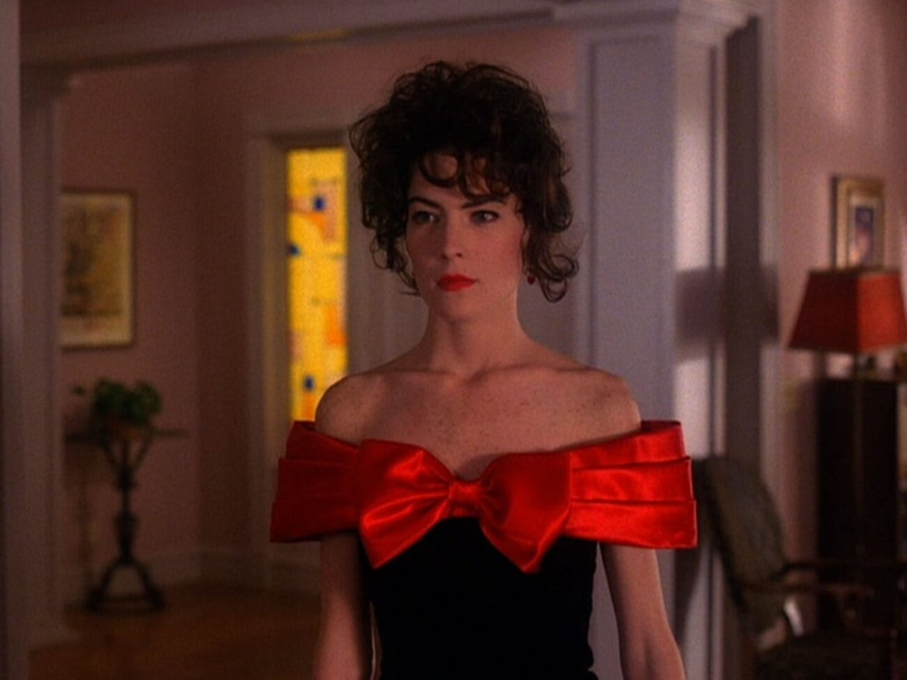 Donna stands in the Hayward living room wearing a prom dress with a big red bow