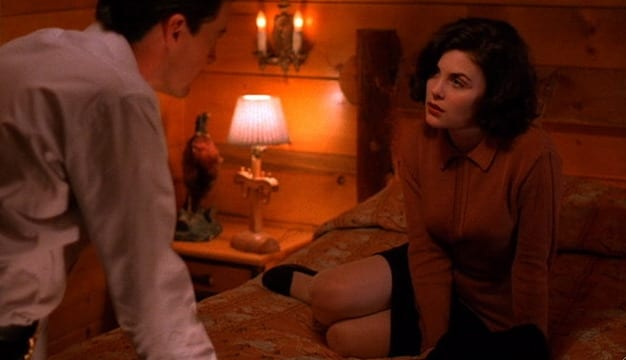Audrey sits on Cooper's bed as he leans towards her