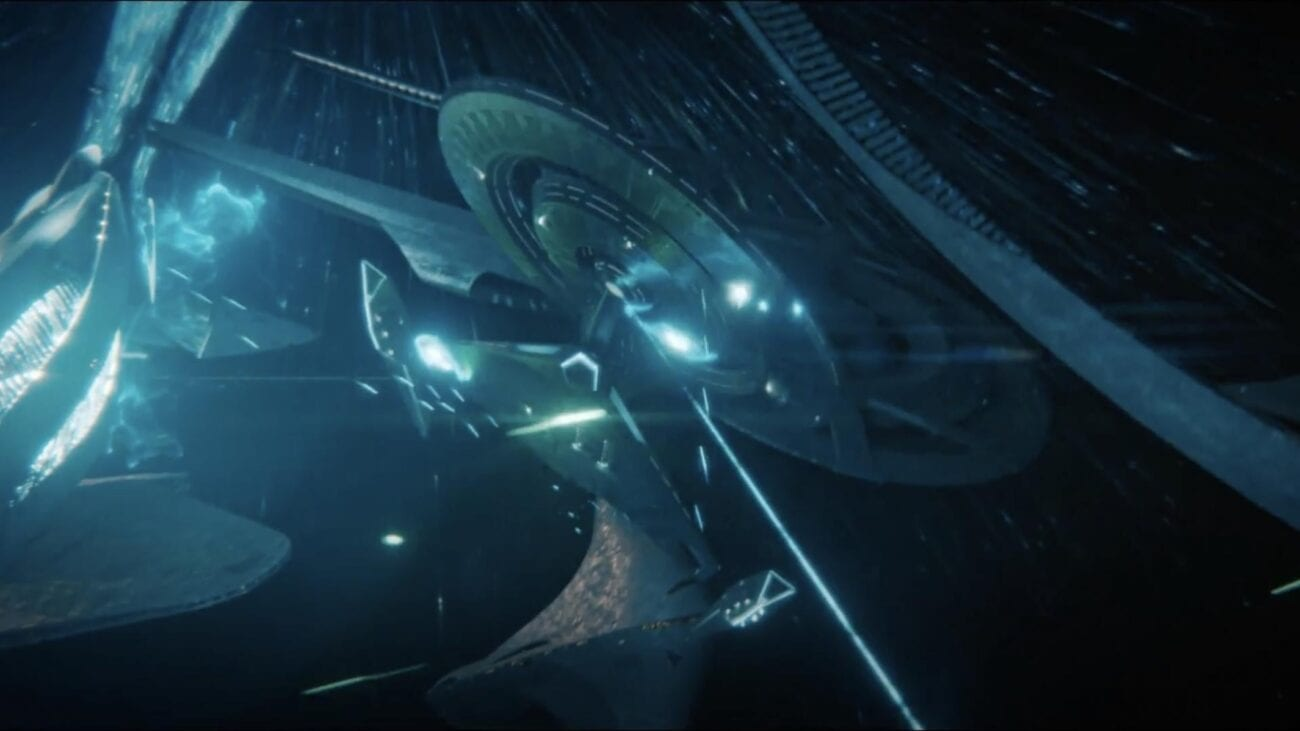 Discovery in blue light being hit by a phaser beam with the Federation headquarters in the background