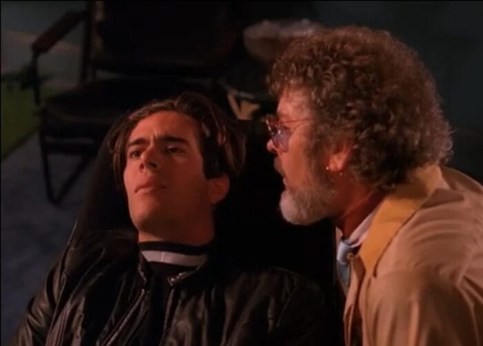 Bobby lays on the couch with an aggrieved look on his face, while Jacoby leans in close to him, speaking in his ear, in Twin Peaks Episode 5