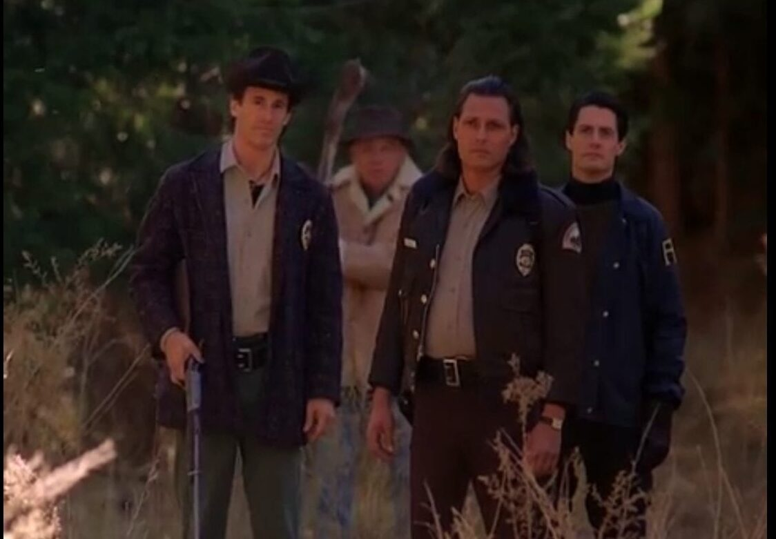 Harry, Doc, Hawk, and Cooper stand in tall grass all facing the screen. Harry carries a shotgun.