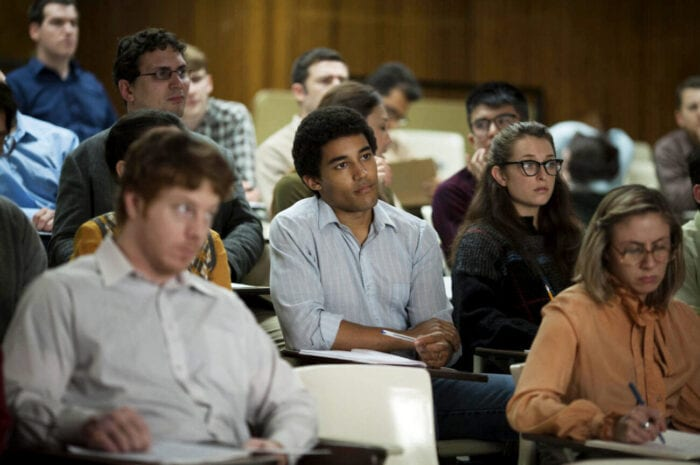 Barry listens from a seat in a lecture hall.