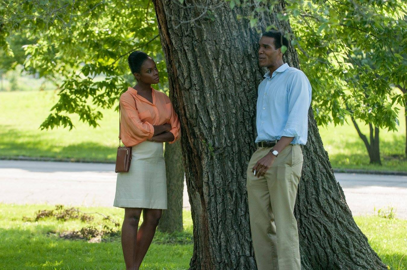 Michelle and Barack share a conversation leaning against a tree.