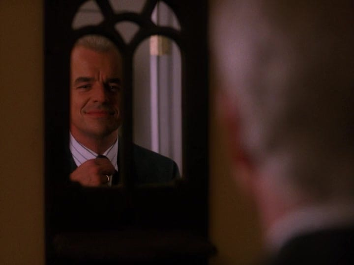 Leland straightens his tie in the mirror