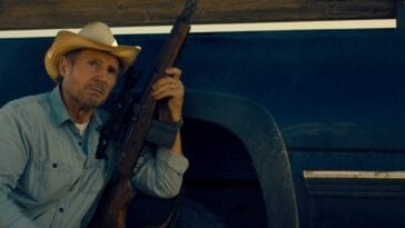 Liam Neeson hunches down next to a truck with his rifle