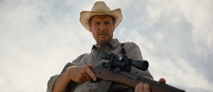 Liam Neeson as Jim, holding a rifle and staring at the ground