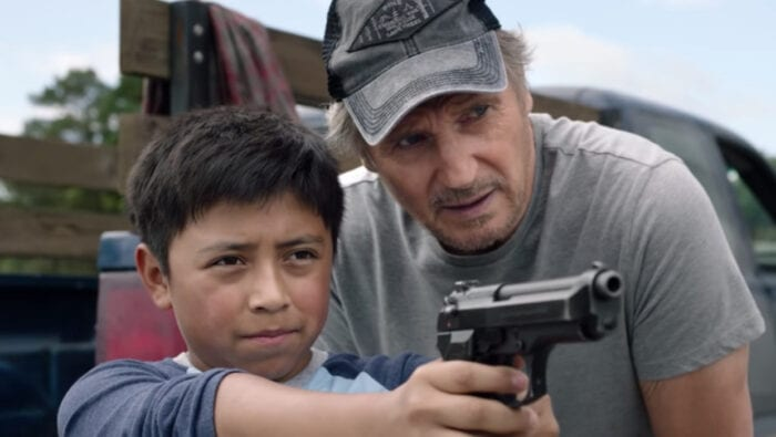 Miguel points a gun at the horizon with Jim looking on, guiding him