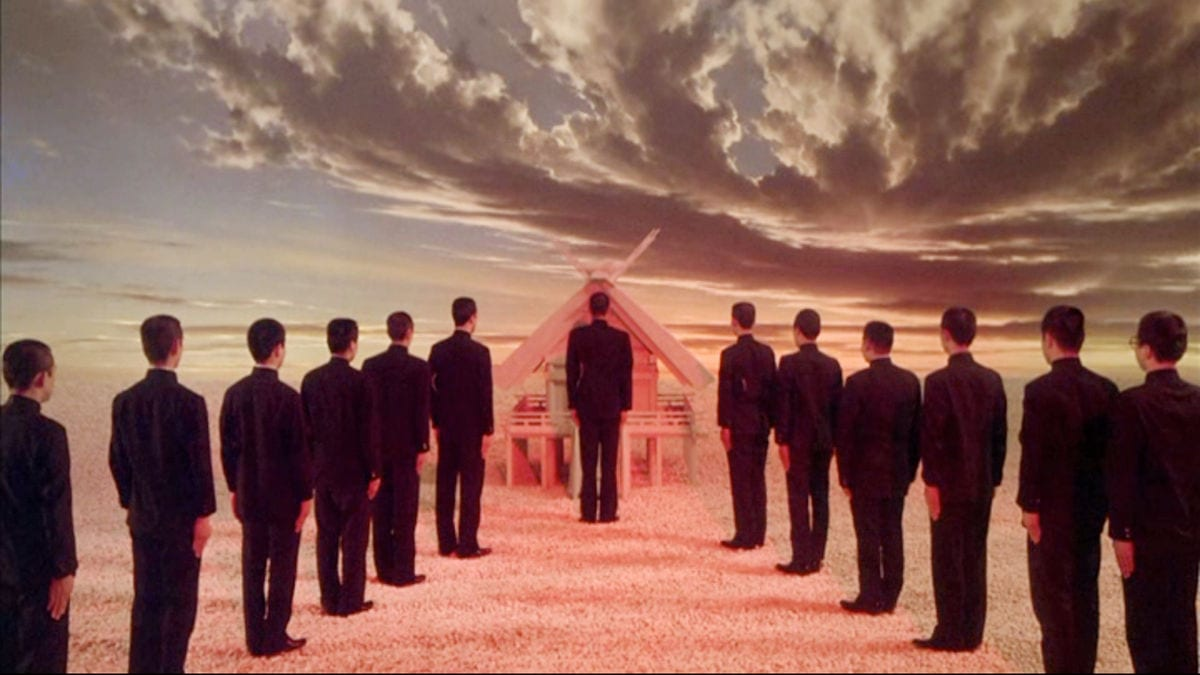 Men stand in two lines approaching a pyramid-like structure in front of a stormy sky in Mishima: A Life in Four Chapters