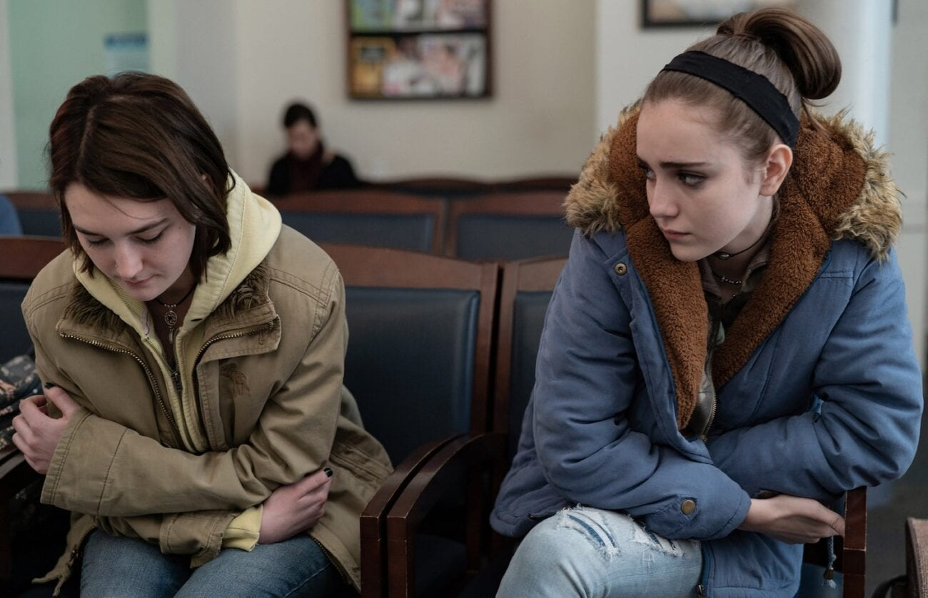 Sidney Flanigan's Autumn sits pensively in a waiting room as her cousin Skylar, played by Talia Ryder looks on sympathetically; Never Rarely Sometimes Always, Focus Features 2020 LLC