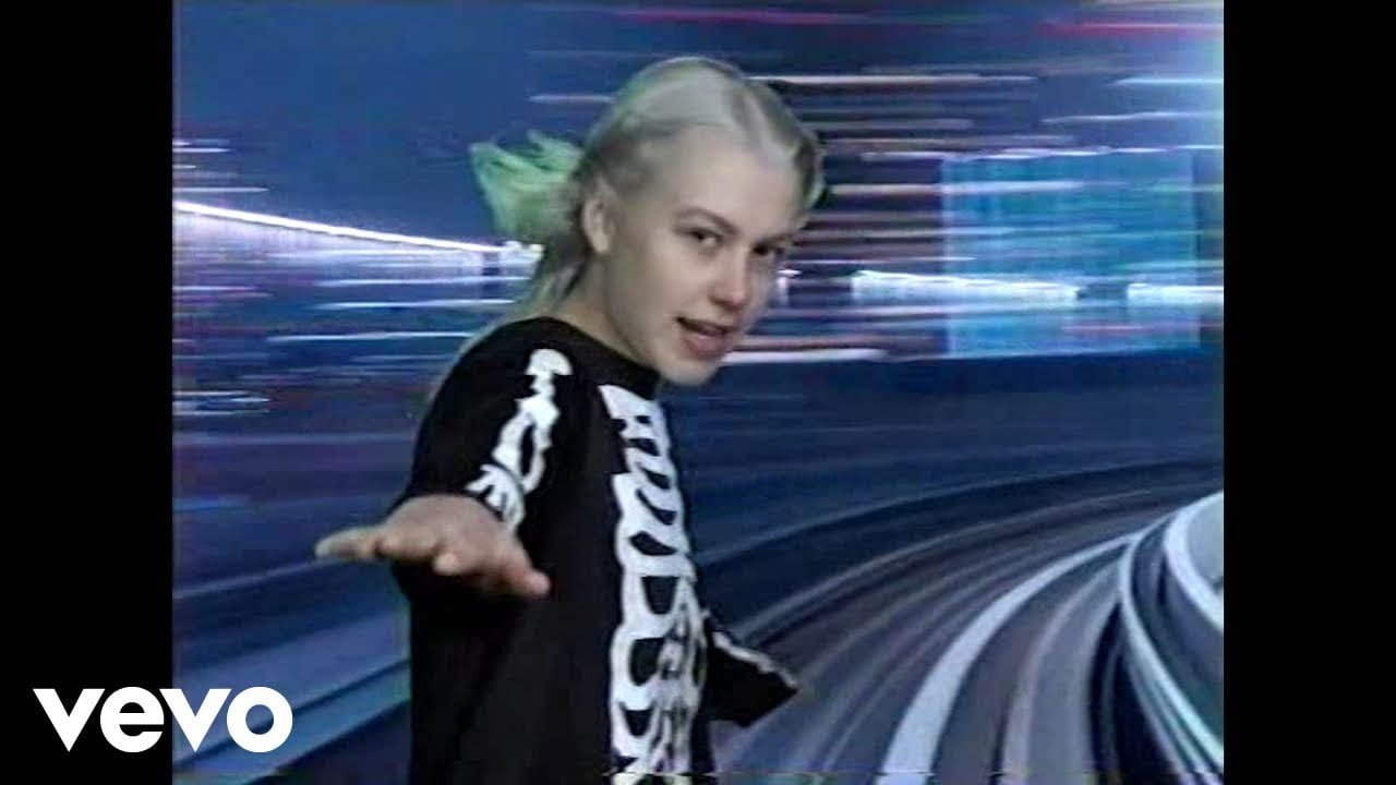 Phoebe Bridgers with an arm outstretched and blurred light in the video for Kyoto