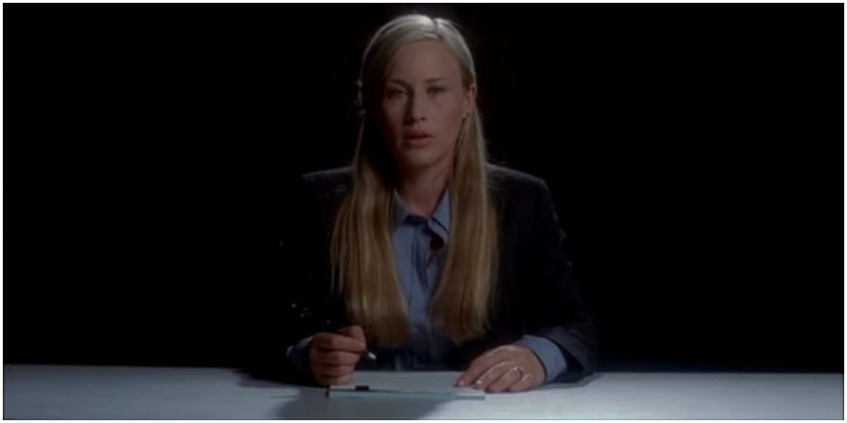 Allison in a suit sitting on opposite side of a table in Medium