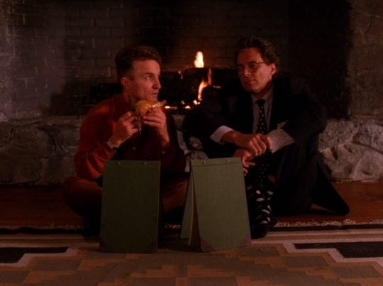 Jerry sits with bin in front of the fire place eating a smoked cheese pig