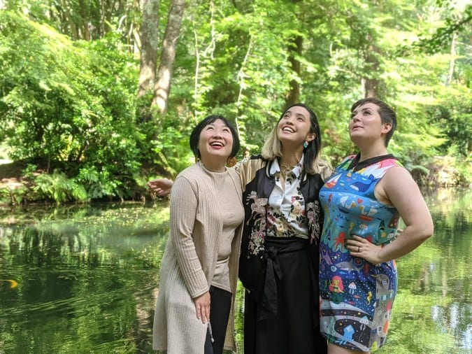 three smiling women stand in front of a pond and trees