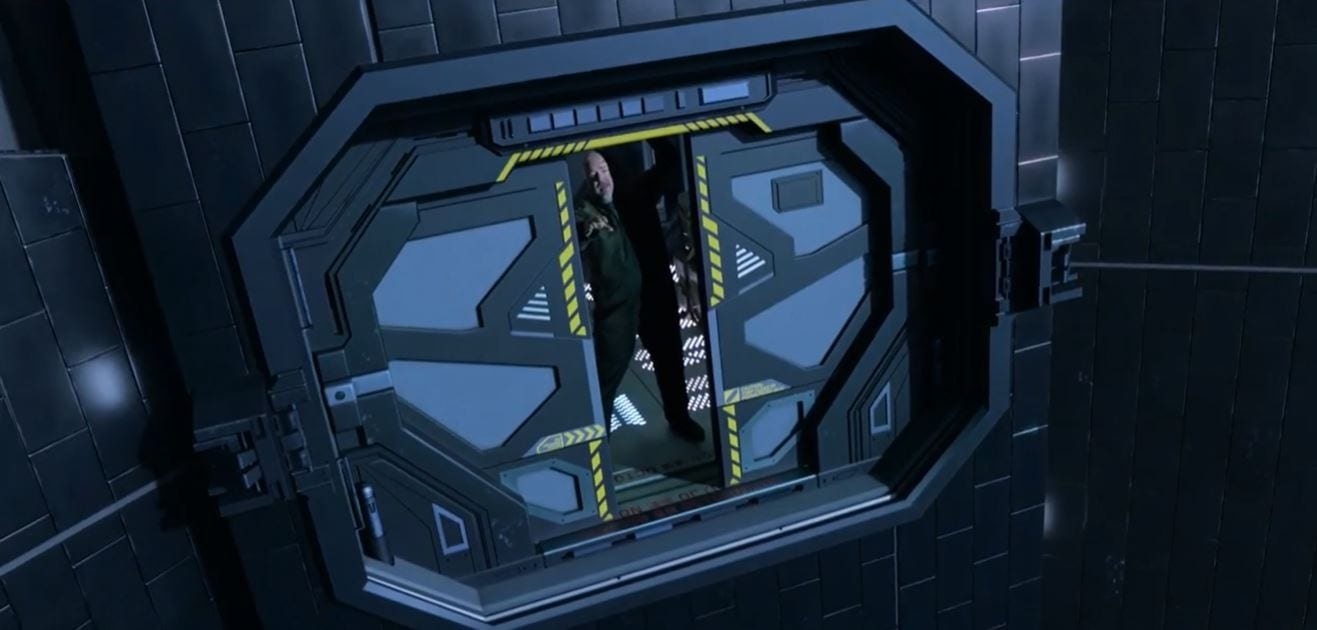Cyn, dead, reaches out from a closing airlock door seen from outside
