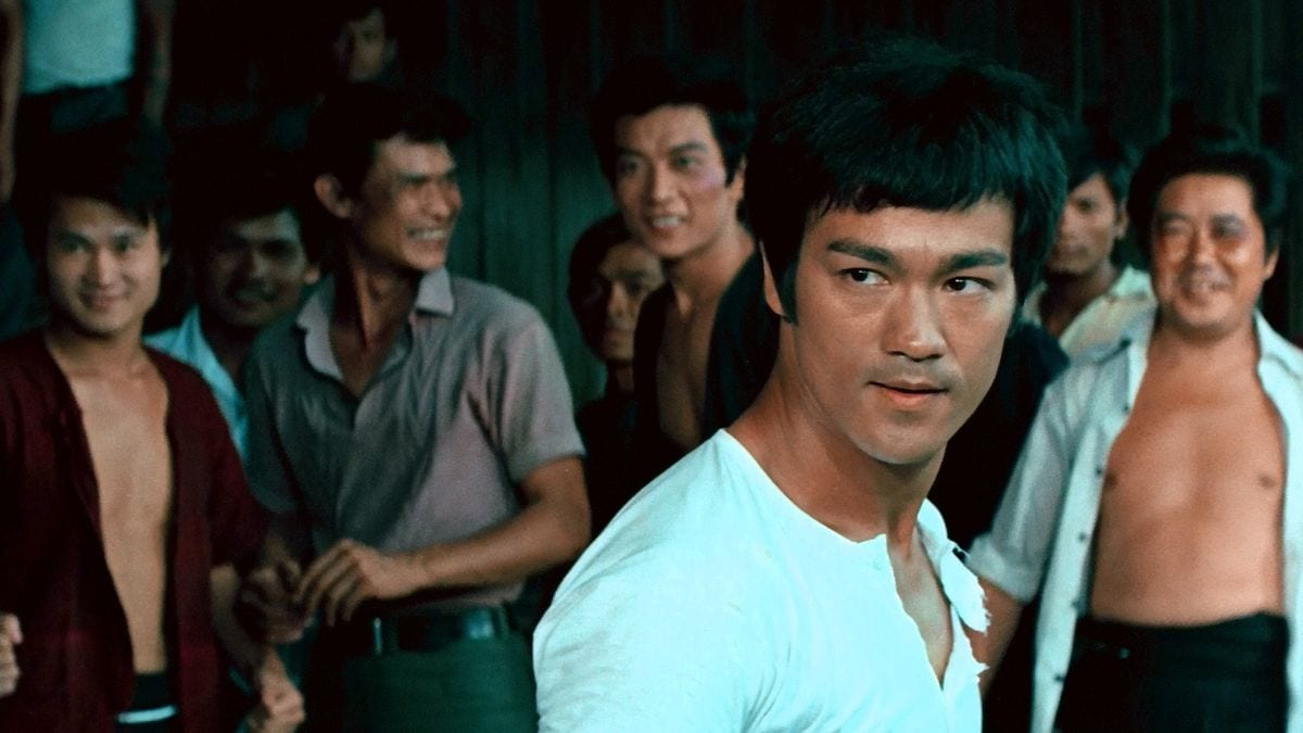 Bruce Lee stands in front of a group of men in The Big Boss