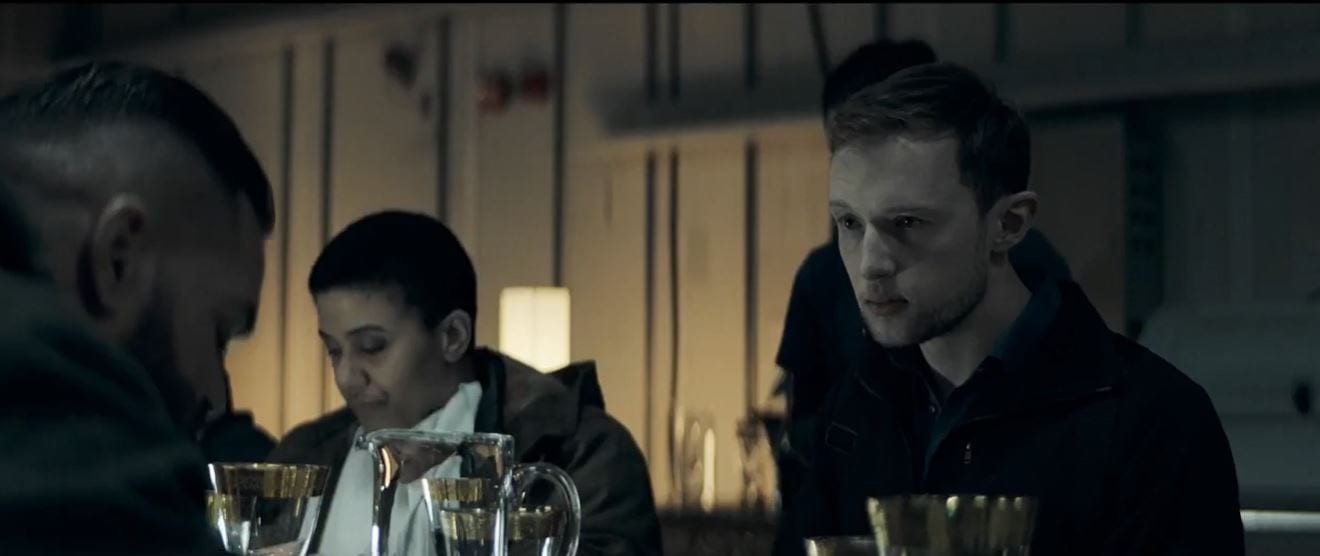 Erich sits at a table eating, next to one of his subordinates