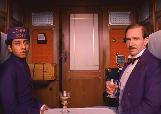 "a young man wearing a purple uniform with ""lobby boy"" embroidered on the hat and a man in a purple tuxedo sit in a train car, looking at the camera. the man holds a small glass."