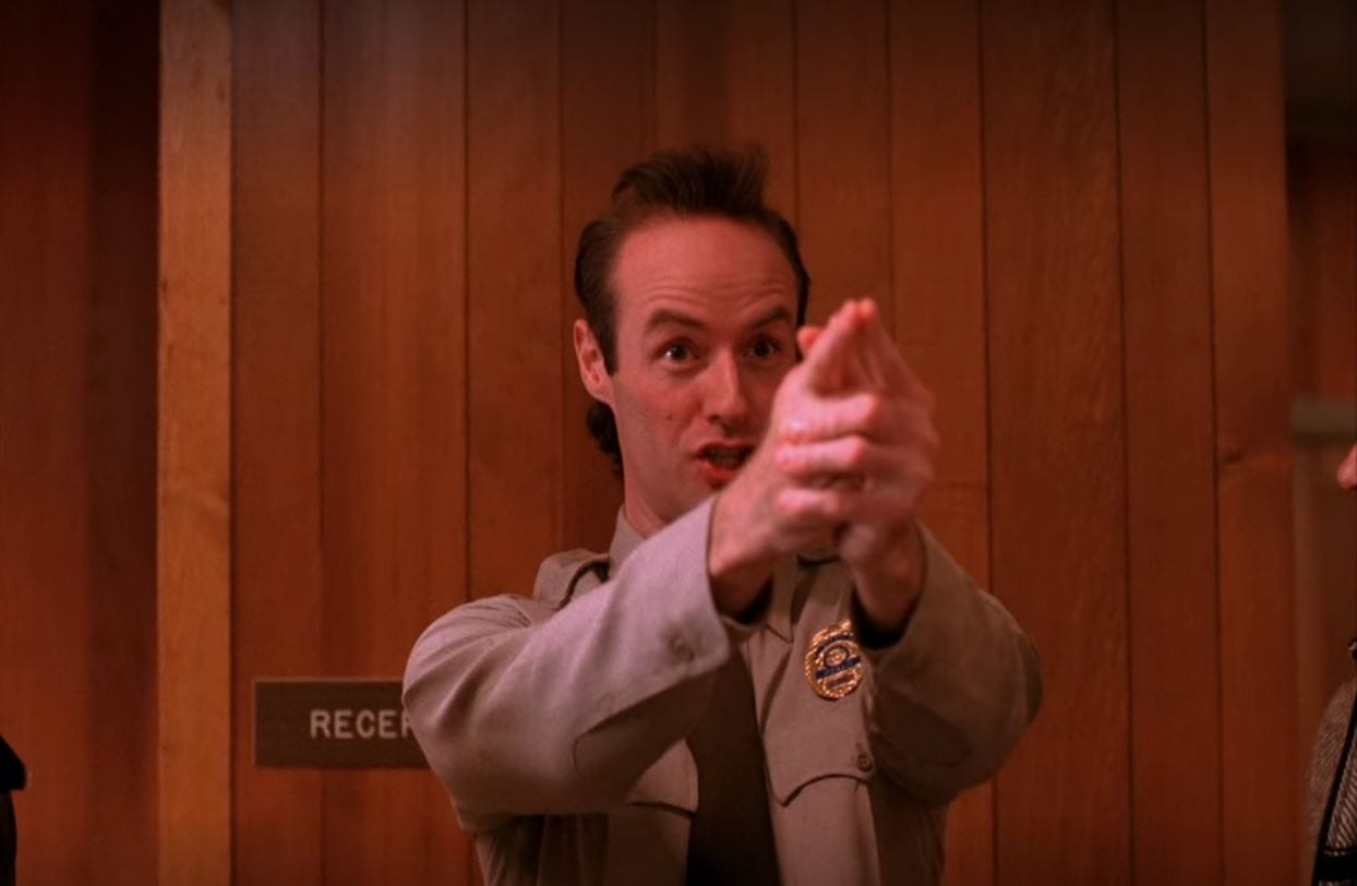 Andy points his fingers in front of him to make a pretend gun as he stands in the Sheriff's station in Twin Peaks