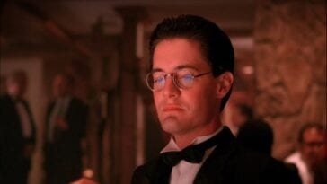 Dale Cooper wears glasses, a suit and a bowtie as he sits gambling at One-Eyed Jacks