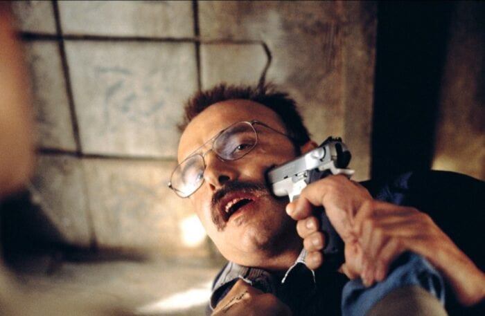 Leonard puts a gun in Teddy's (Joe Napolitano) face.