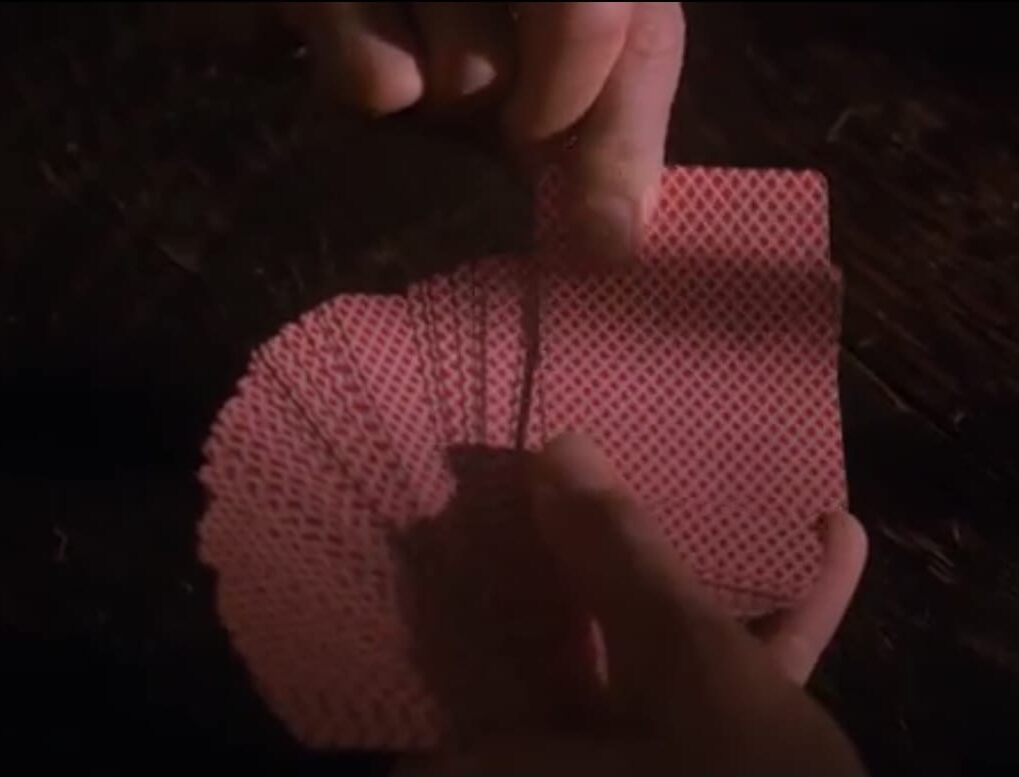 A number of cards spread out by a hand, while another hand pulls one from the deck.