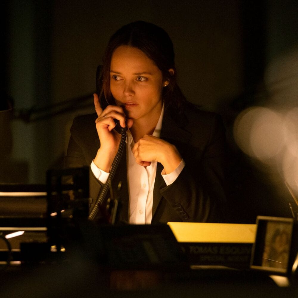 Clarice at a desk in a basement office, on the phone