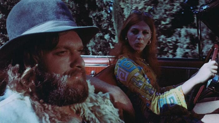 Mike and Elizabeth in American Hippie in Israel. Elizabeth is wearing a colorful shirt while driving. Mike is in the passenger seat wearing his wide-brimmed hat and goat vest.