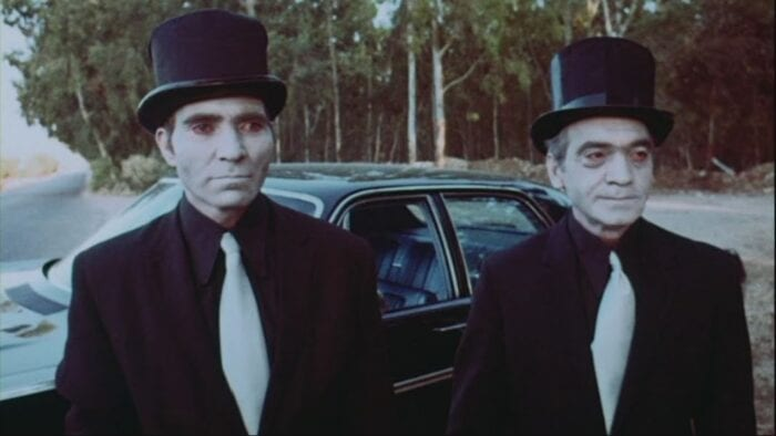 The two mystery men from American Hippie in Israel. Both are wearing black suits, white ties, top hats, and ghostly white face makeup.