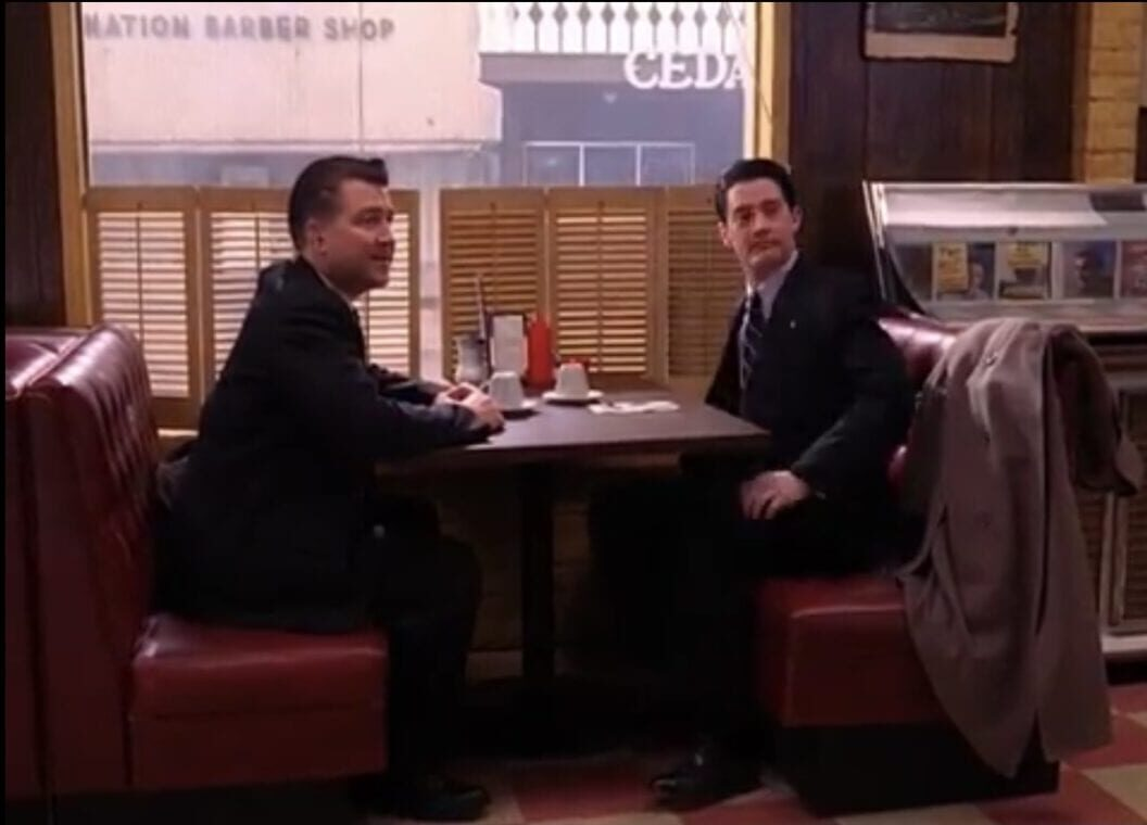 Dale and Gordon in their black suits, sit in a booth while regarding someone offscreen.
