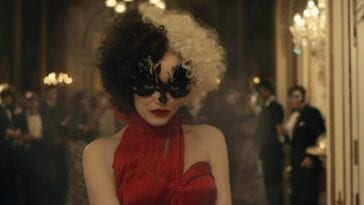 Cruella with her half black and half white hair stares at the camera in a red dress and black mask