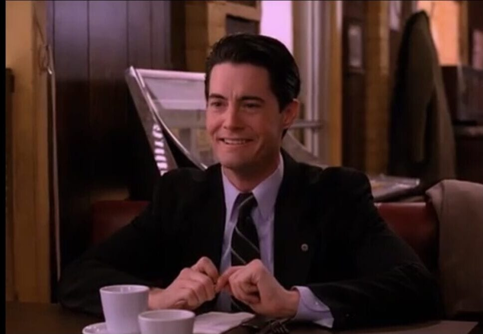 Dale Cooper grins in a booth at the Double R while thinking about Annie.