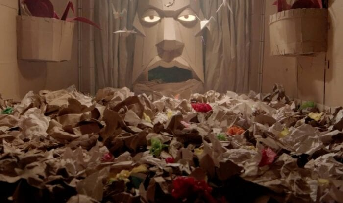 piles of cardboard and paper fill a room. in the back is a giant face set into the wall with glowing eyes, also made of cardboard
