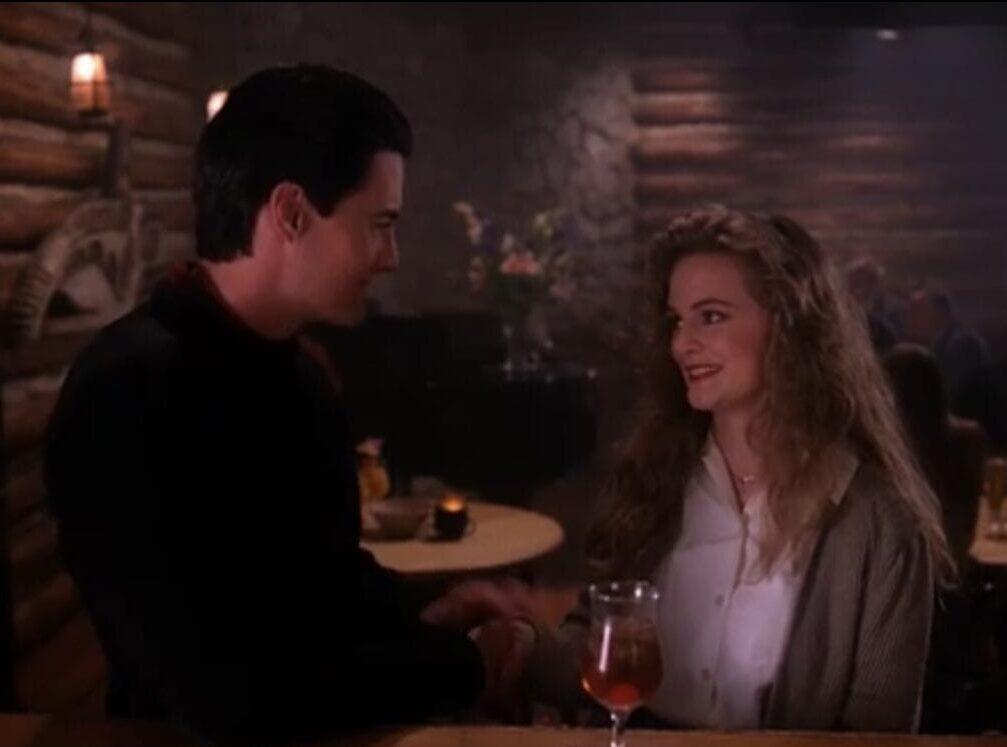 Cooper in dark spelunking clothes, and Annie in white blouse and gray sweater, flirting and smiling at each other.
