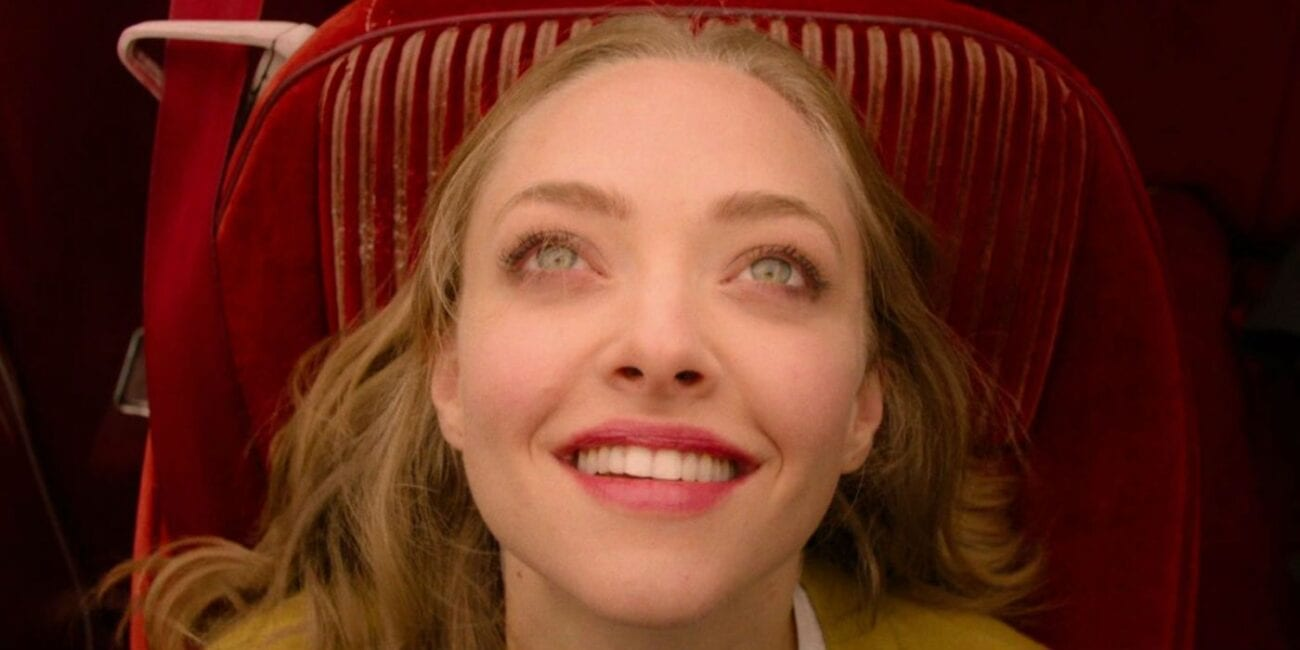 A young blonde woman smiling in a blissful state while looking to the sky from her seat in a car